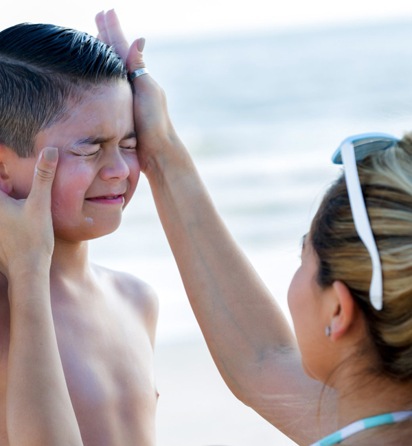 mother applying sunscreen on her son